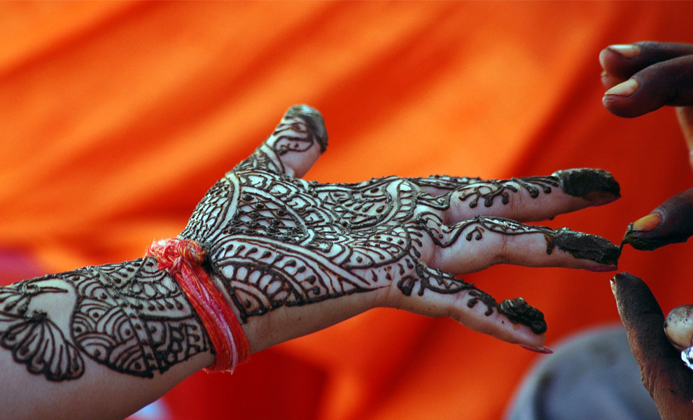 Ind A Hindu woman has her hand painted with henna during the Teej festival in the northern Indian city of Allahabad September 2, 2008 REUTERSJitendra Prakash