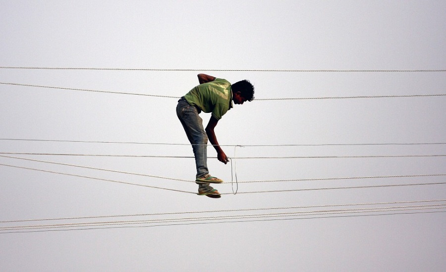 A power company worker stands on electricity transmission lines while making adjustments in the city of Sangam in Allahabad, India, ahead of the Maha Kumbh Mela festival. AFP