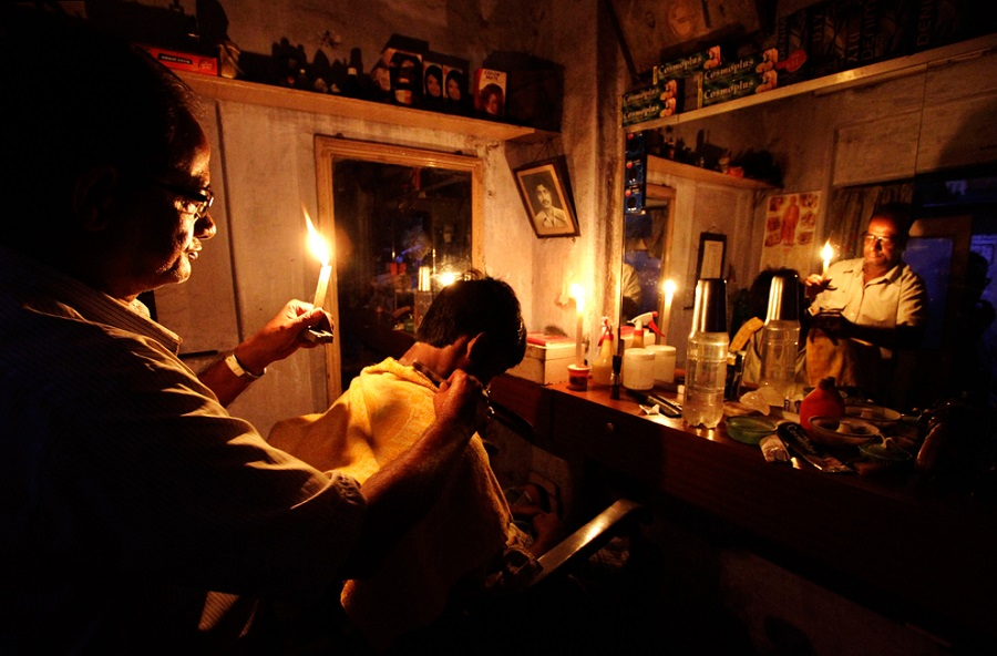 An Indian barber holding a candle, has a haircut for a customer at his shop in Kolkata, India, Tuesday, July 31, 2012. India's energy crisis  Bikas DasAssociated Press