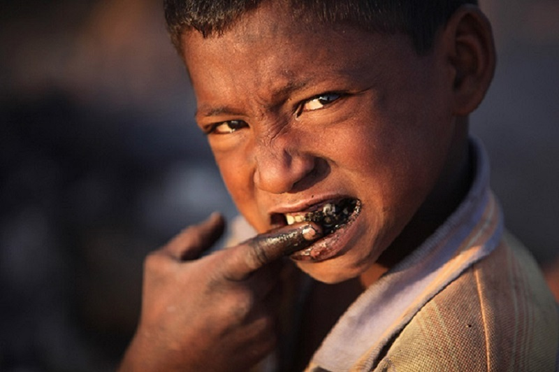 A homeless boy cleans his teeth with coal