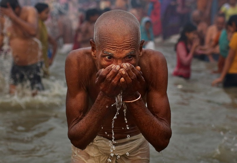 A man drinks as he prays at Sangam on January 14, 2013Kevin FrayerAssociated Press