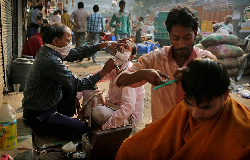Haircuts are administered by street barbers at a marketplace in New Delhi, India, on November 9, 2012.KevinFrayerAP